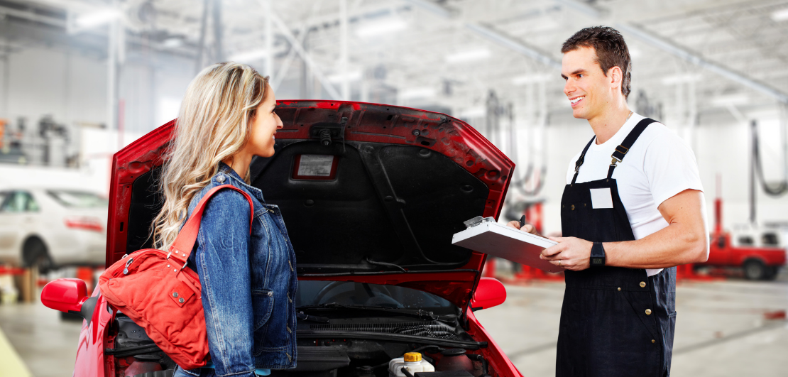 Auto mechanic talking to a client in front of a red car