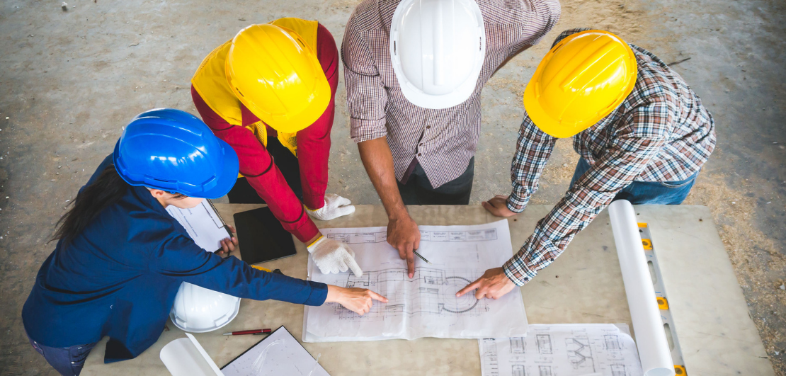 Contractors wearing safety helmets looking at blueprints on table