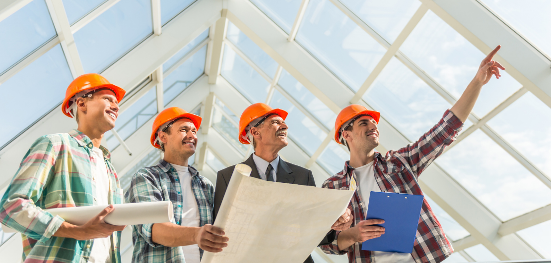 4 contractors looking up through a glass roof