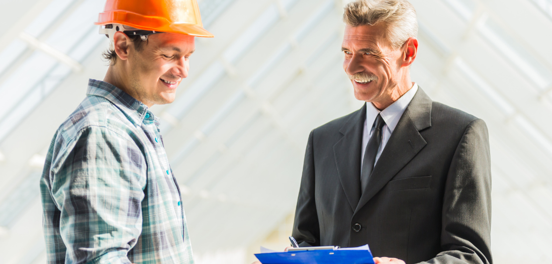 A contractor and a man in a suit looking at a document
