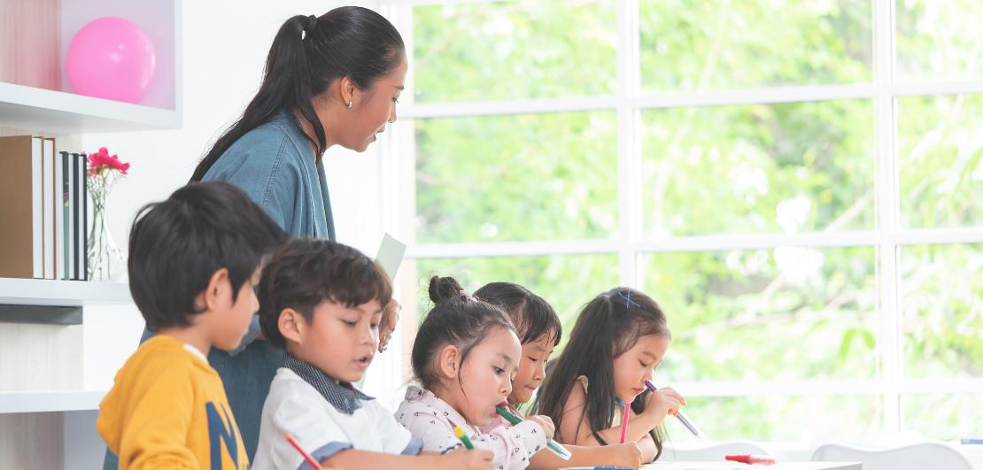 A teacher teaching children at a kindergarten