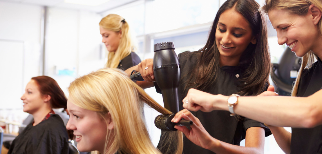 Hairdressers blowdrying a female client's long hair.
