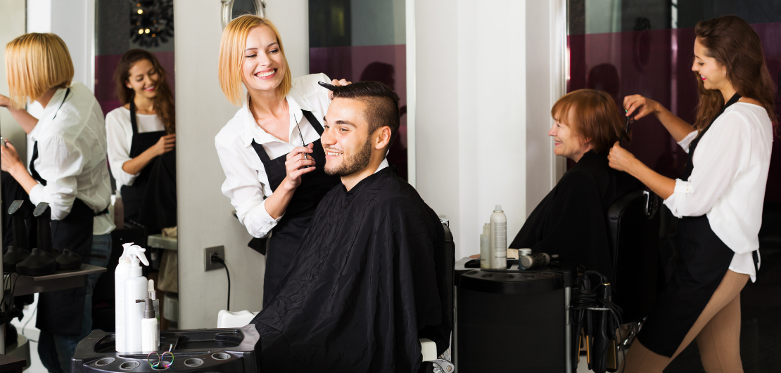 A smiling female hairdresser giving a male client a haircut.