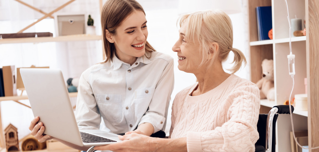 A younger woman assisting an older woman with the computer