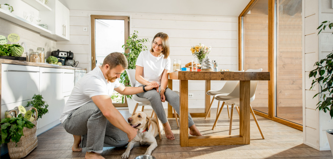 A happy couple interacting with their dog in their kitchen/dining room.