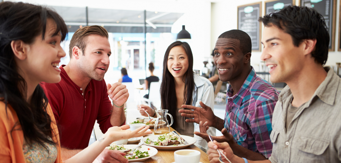 Five people around a table at restaurant in the middle of a conversation while having a conversations