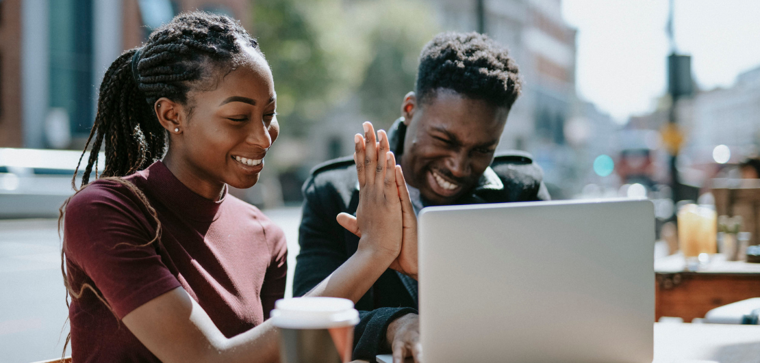 A smiling man and a woman behind a laptop giving each other a high five