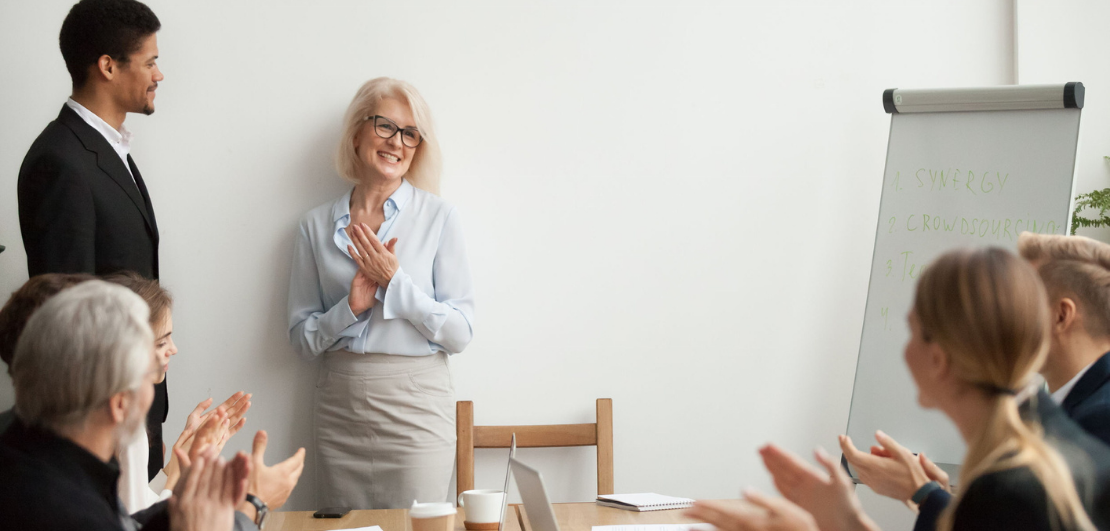 A happy woman standing next to the wall and facing her coworkers who are applauding